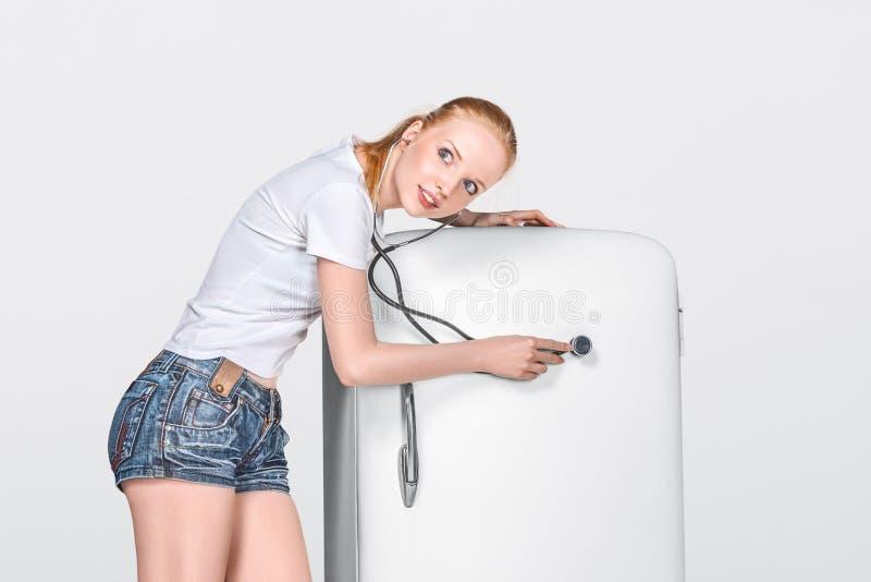 Jeune femme et réfrigérateur fermé image stock