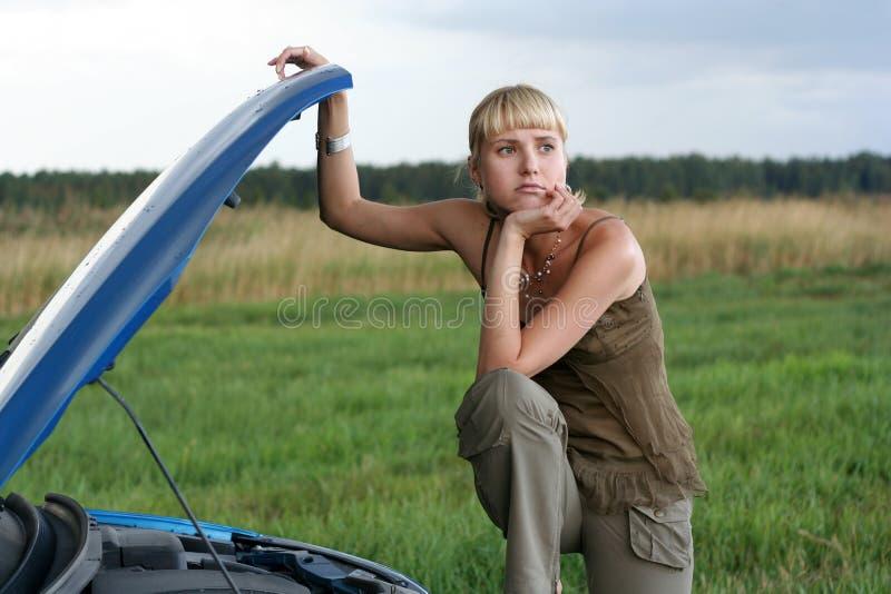 Jeune femme et son véhicule cassé photographie stock libre de droits