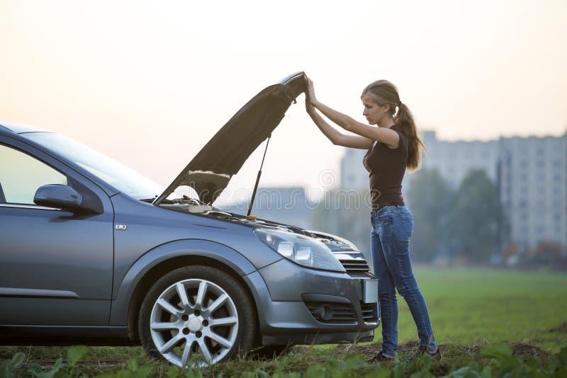 Jeune femme et une voiture avec le capot sauté Transport, problèmes de véhicules et concept de pannes photos libres de droits