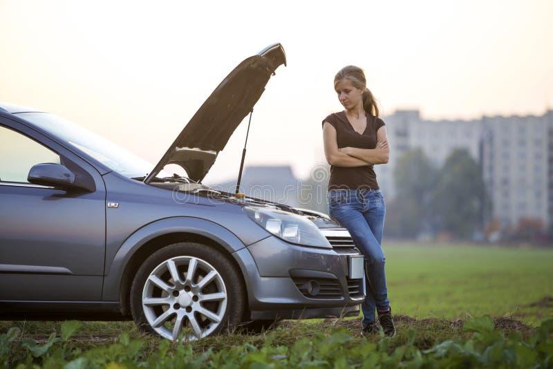 Jeune femme et une voiture avec le capot sauté Transport, problèmes de véhicules et concept de pannes photographie stock libre de droits