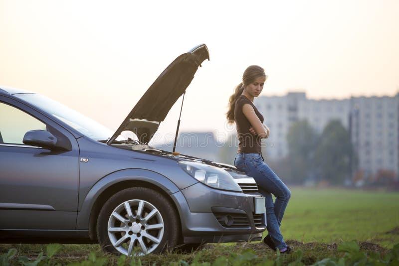 Jeune femme et une voiture avec le capot saut? Transport, probl?mes de v?hicules et concept de pannes images stock