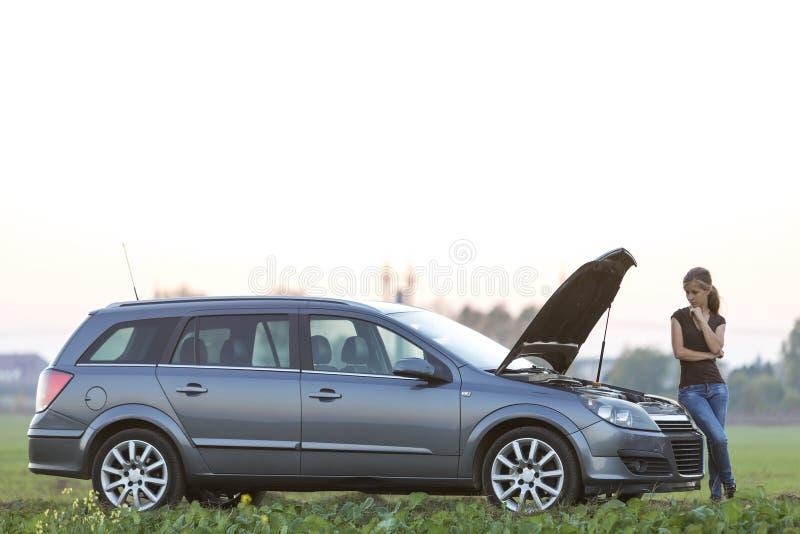 Jeune femme et une voiture avec le capot saut? Transport, probl?mes de v?hicules et concept de pannes photographie stock