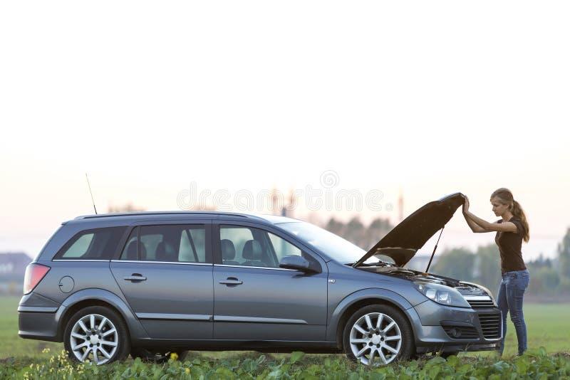 Jeune femme et une voiture avec le capot saut? Transport, probl?mes de v?hicules et concept de pannes image stock