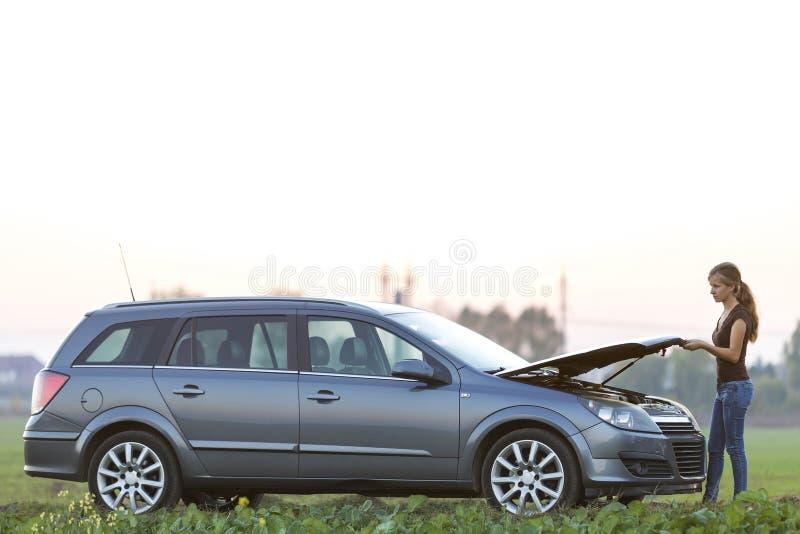 Jeune femme et une voiture avec le capot saut? Transport, probl?mes de v?hicules et concept de pannes photos libres de droits