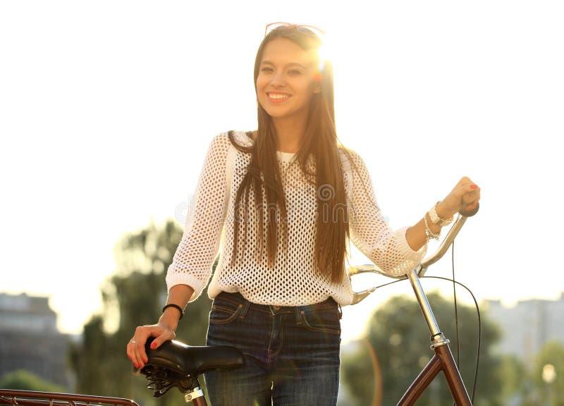 Jeune femme et vélo dans la ville photographie stock