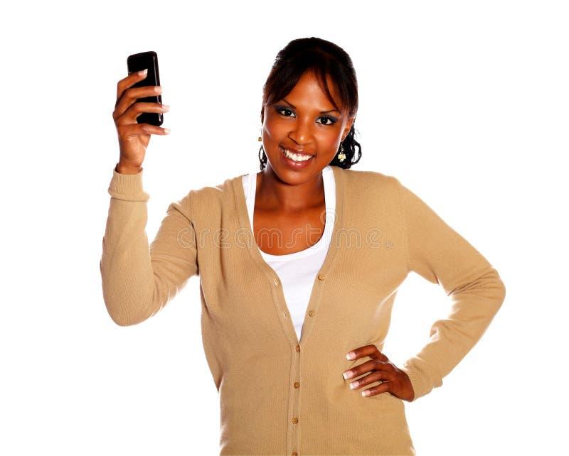 Jeune femme ethnique supportant son portable photographie stock