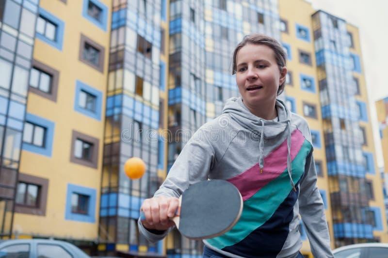 Jeune femme européenne jouant au ping-pong dans la cour photo stock