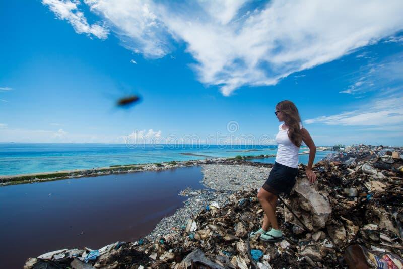 Jeune femme européenne s'asseyant au bord de la décharge de déchets photographie stock libre de droits