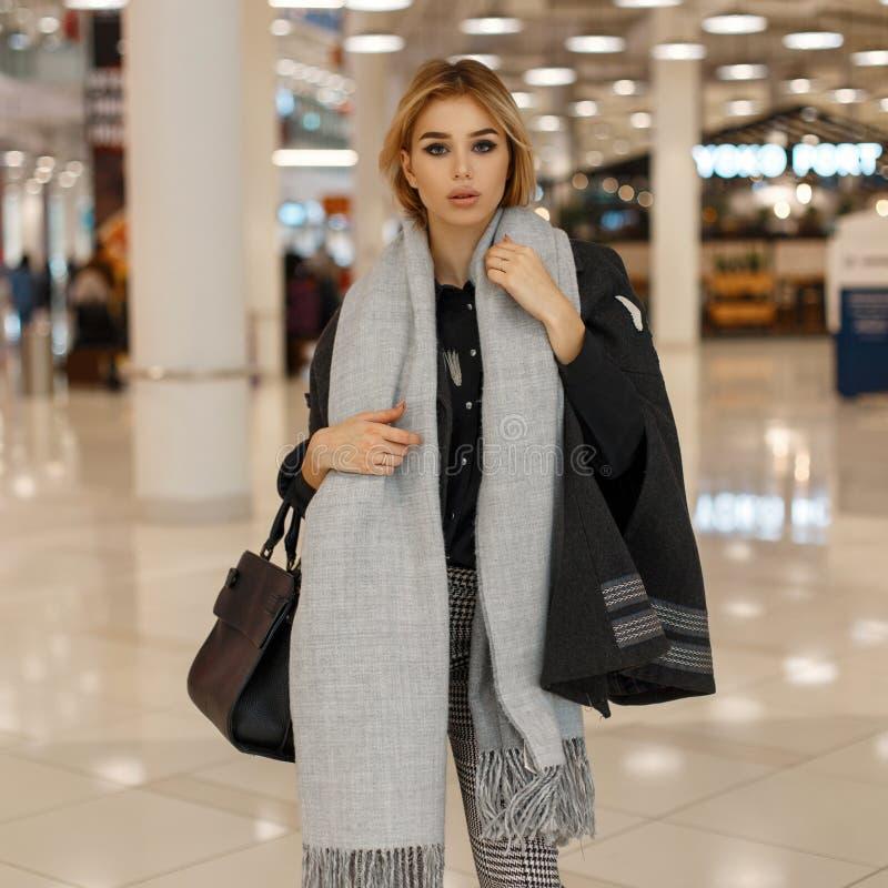 Jeune femme européenne urbaine dans un manteau élégant gris avec une écharpe à la mode de cru avec un sac à main noir en cuir images stock
