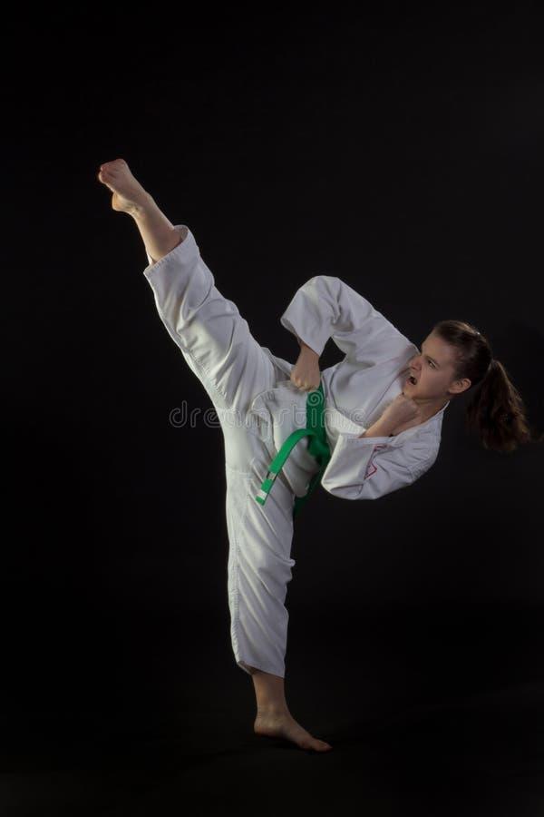 Jeune femme exécutant le coup-de-pied élevé du Taekwondo photographie stock libre de droits