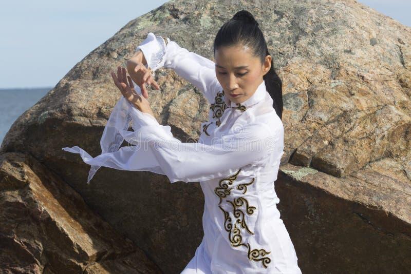 Jeune femme exécutant le gong de Qi sur une plage rocheuse du Connecticut photos stock