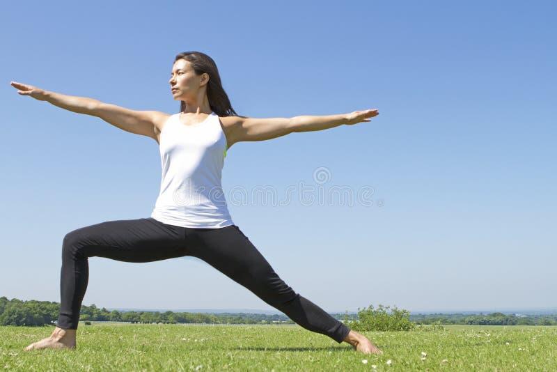 Jeune femme exécutant une pose de guerrier de yoga photo stock