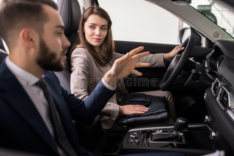 Jeune femme examinant la nouvelle voiture dans la salle d'exposition image stock