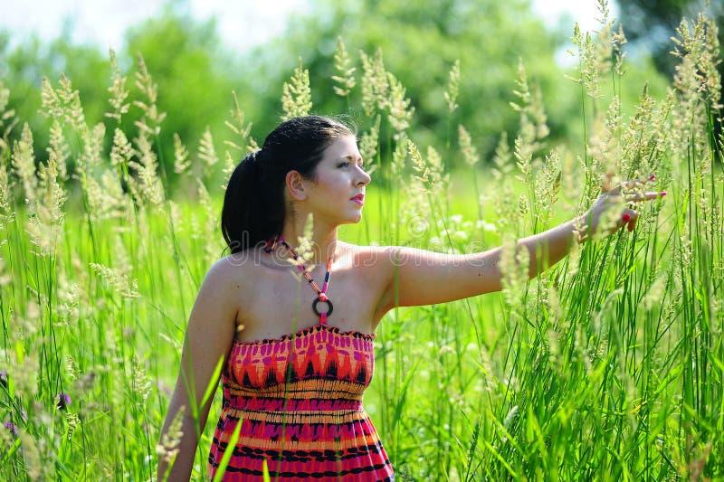 Jeune femme extérieur dans l'herbe dans l'été photographie stock libre de droits