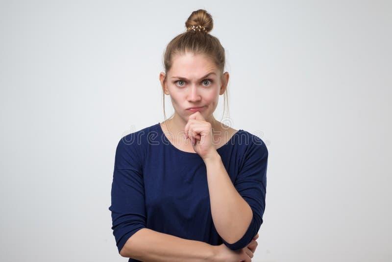 Jeune femme fâchée sérieuse avec le petit pain de cheveux semblant méfiant image stock