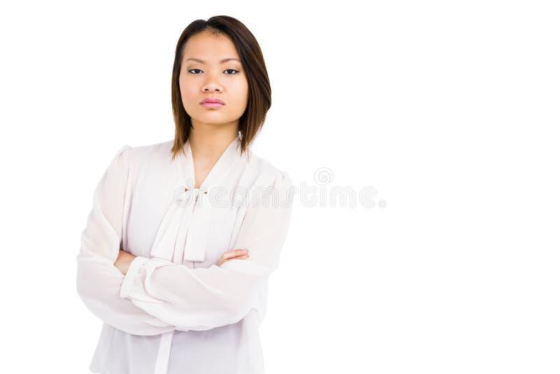 Jeune femme fâchée se tenant avec des bras croisés image stock
