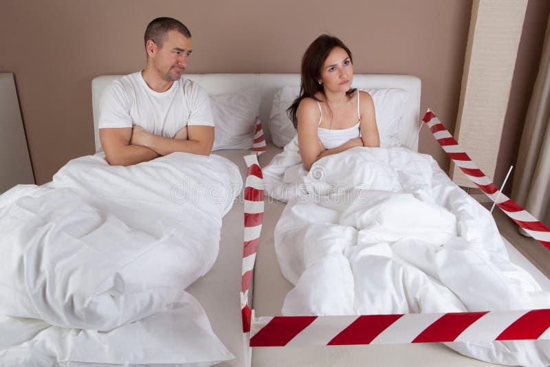 Jeune femme fâchée se trouvant séparément du mari sur le lit image libre de droits
