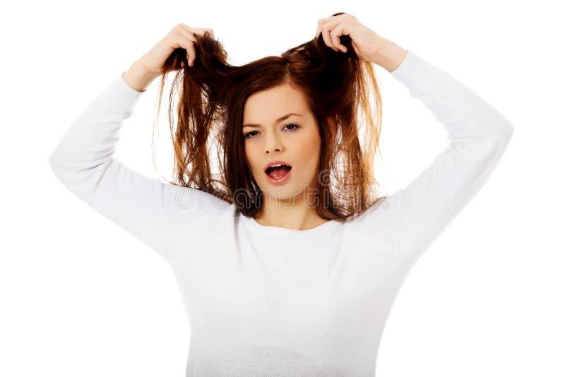Jeune femme fâchée tirant ses cheveux images stock