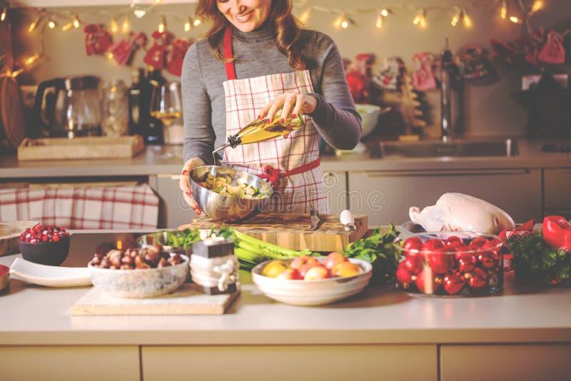 Jeune femme faisant cuire dans la cuisine Nourriture saine pour le canard ou l'oie bourré par Noël image libre de droits