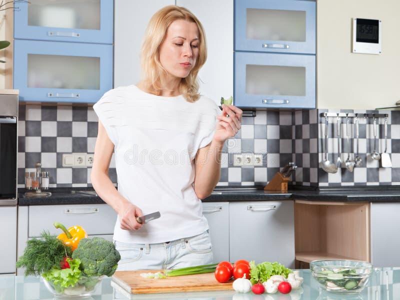 Jeune femme faisant cuire la nourriture et le morceau d'essai sains image libre de droits