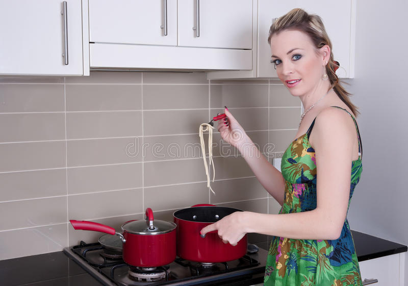 Jeune femme faisant cuire le dîner images libres de droits