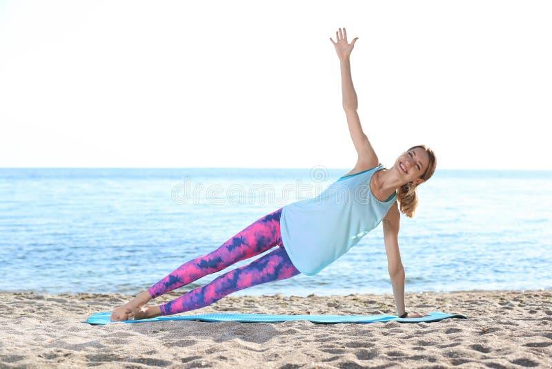 Jeune femme faisant des exercices de yoga sur la plage images libres de droits