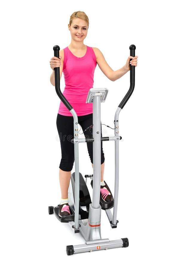 Jeune femme faisant des exercices sur l'avion-école elliptique photographie stock