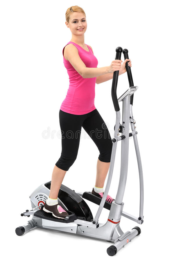 Jeune femme faisant des exercices sur l'entraîneur elliptique images libres de droits