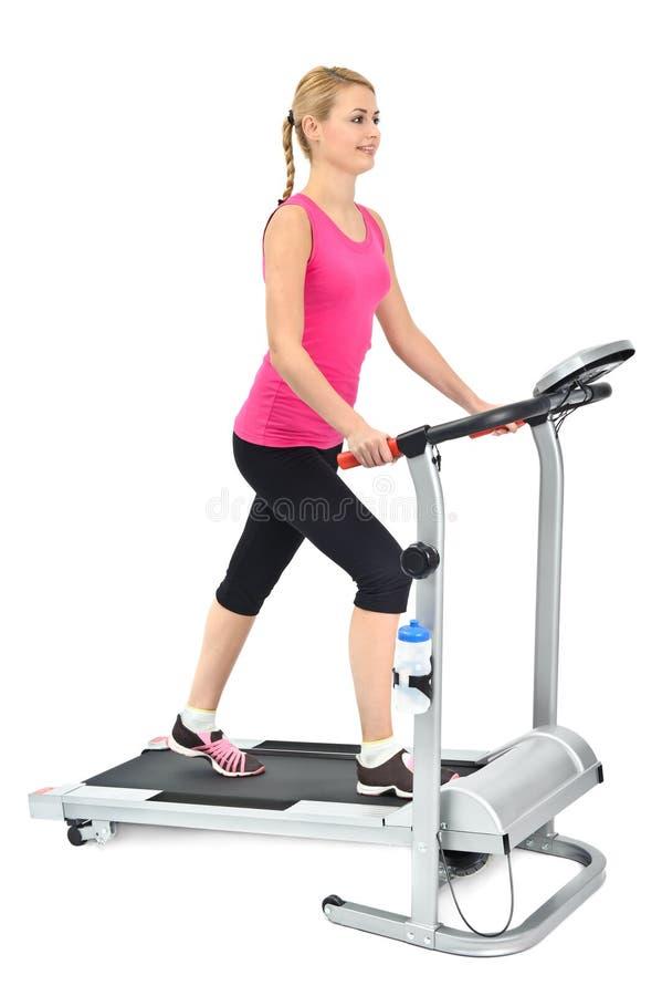 Jeune femme faisant des exercices sur le tapis roulant photographie stock