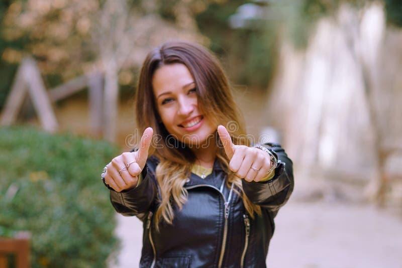 Jeune femme faisant des gestes le pouce en parc photo libre de droits
