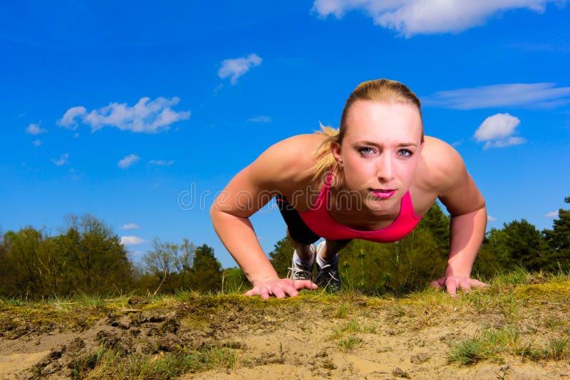 Jeune femme faisant des pousées dehors photographie stock libre de droits