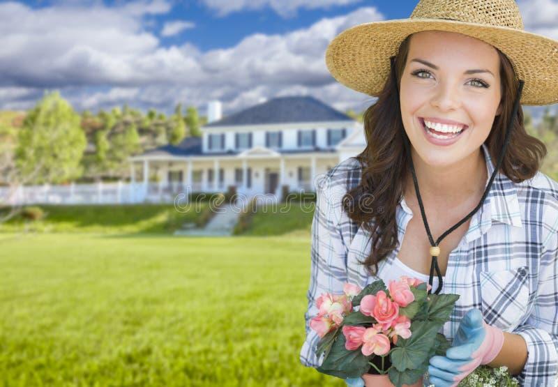 Jeune femme faisant du jardinage devant la belle Chambre photo stock