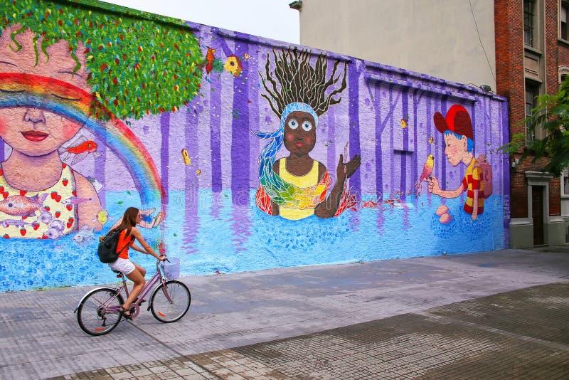 Jeune femme faisant du vélo le long du mur coloré à Montevideo, Uruguay photographie stock