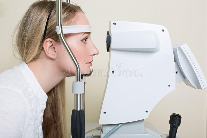 Jeune femme faisant examiner ses yeux par un oeil images libres de droits