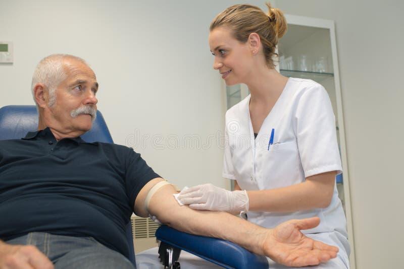 Jeune femme faisant l'analyse de sang pour l'homme supérieur avec du diabète photo libre de droits