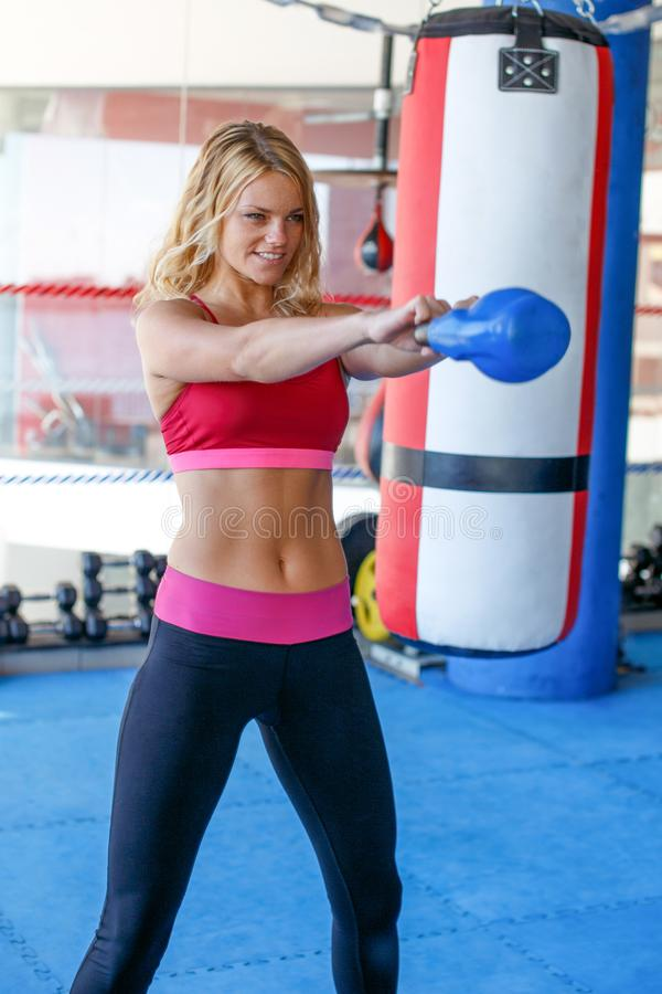 Jeune femme faisant l'exercice avec le kettlebell dans le gymnase photo stock