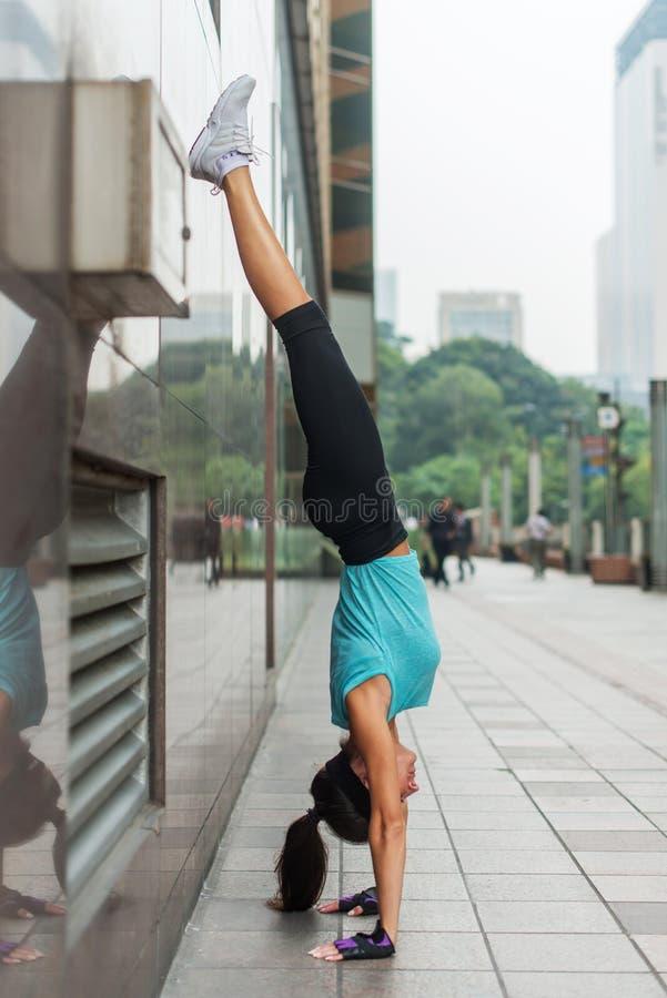 Jeune femme faisant l'exercice d'appui renversé contre le mur sur la rue de ville images stock