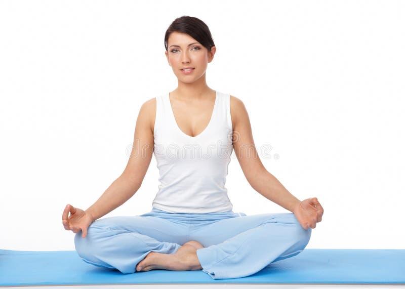 Jeune femme faisant l'exercice de yoga sur le couvre-tapis bleu images stock