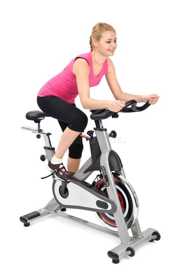 Jeune femme faisant l'exercice faisant du vélo d'intérieur image stock