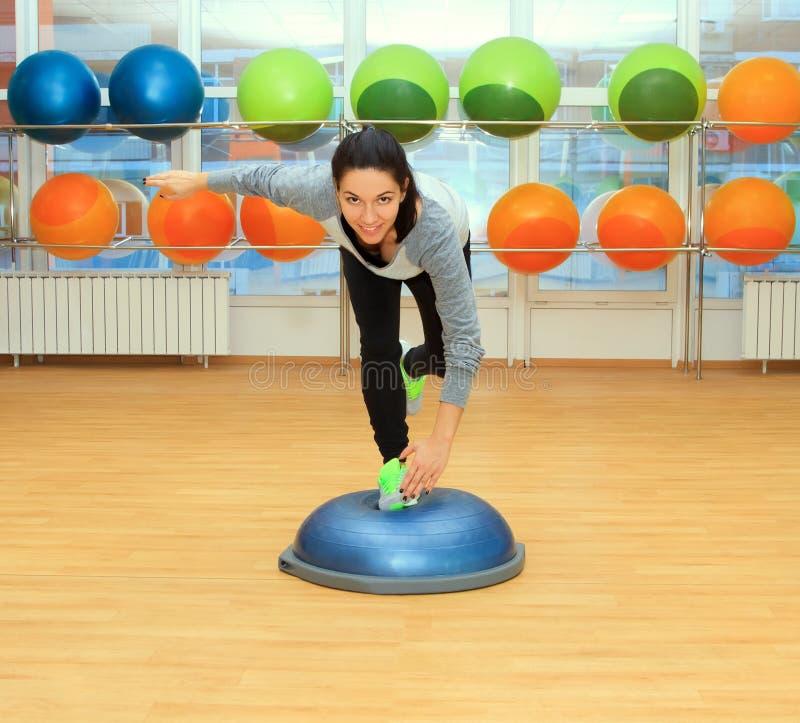 Jeune femme faisant l'exercice sur la boule d'ajustement photos libres de droits