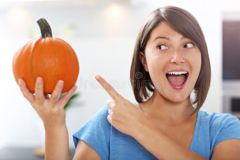 Jeune femme faisant la cric-o-lanterne dans la cuisine image stock