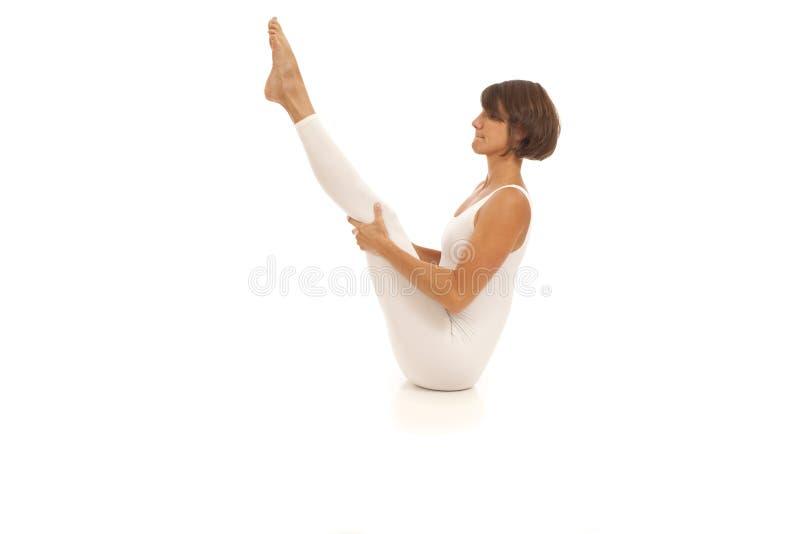 Jeune femme faisant la pose de bateau de Navasana de yoga photos stock