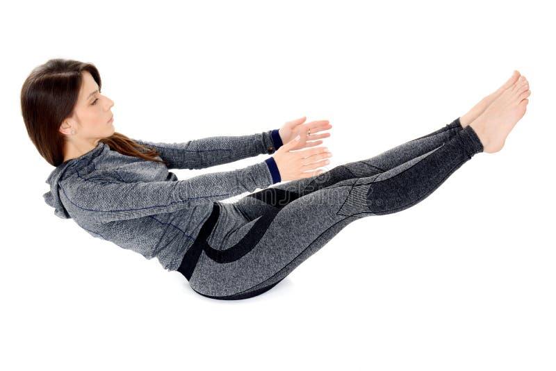Jeune femme faisant la pose de bateau de Navasana d'asana de yoga images libres de droits