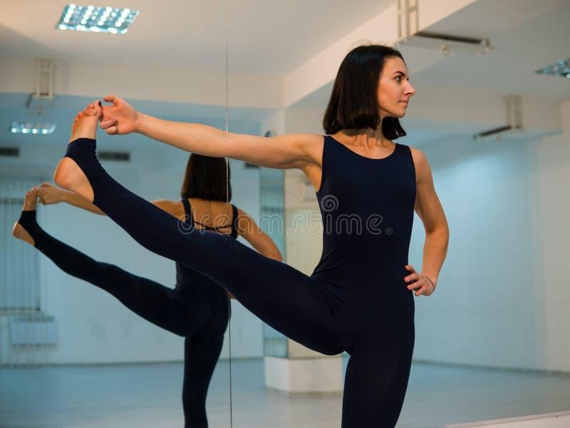 Jeune femme faisant la pose et l'asana de yoga Belle femme appréciant le yoga à l'intérieur dans des vêtements de sport, établiss photos stock