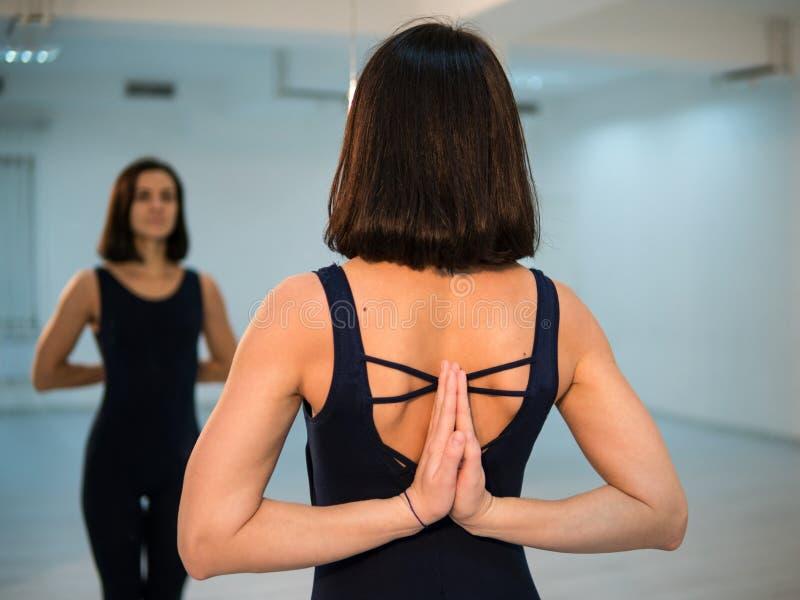 Jeune femme faisant la pose et l'asana de yoga Belle femme appréciant le yoga à l'intérieur dans des vêtements de sport, établiss image stock