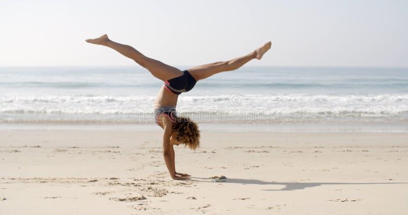 Jeune femme faisant la roue sur la plage images libres de droits