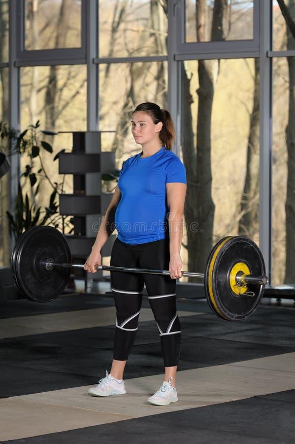 Jeune femme faisant la séance d'entraînement de deadlift avec le barbell lourd dans le gymnase foncé images stock