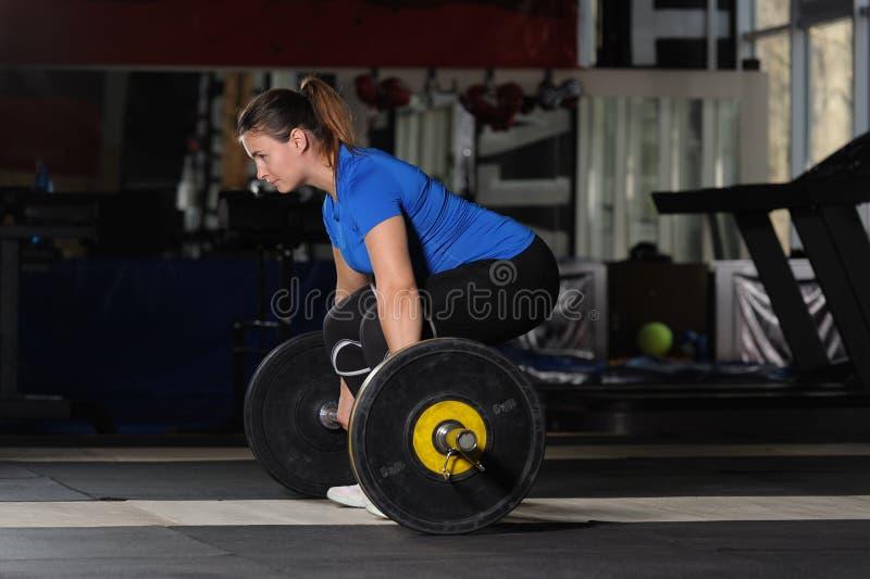 Jeune femme faisant la séance d'entraînement de deadlift avec le barbell lourd dans le gymnase foncé photos libres de droits