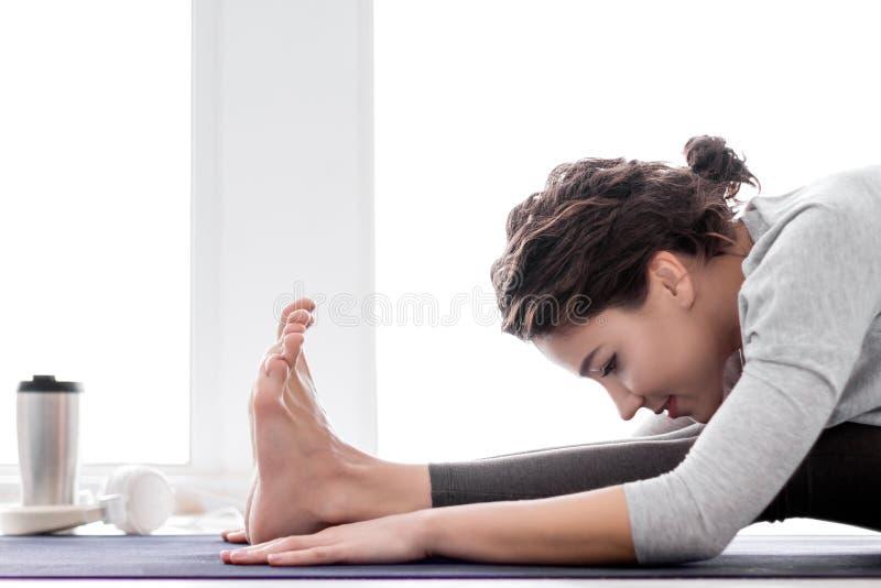 Jeune femme faisant la s?ance d'entra?nement de yoga ? la maison image stock