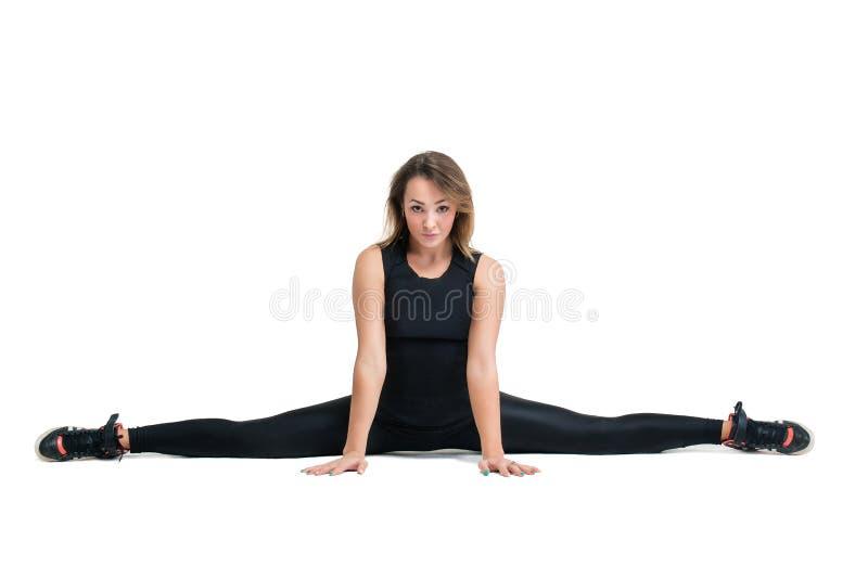 Jeune femme faisant le côté dédoublé dans la classe de forme physique images stock